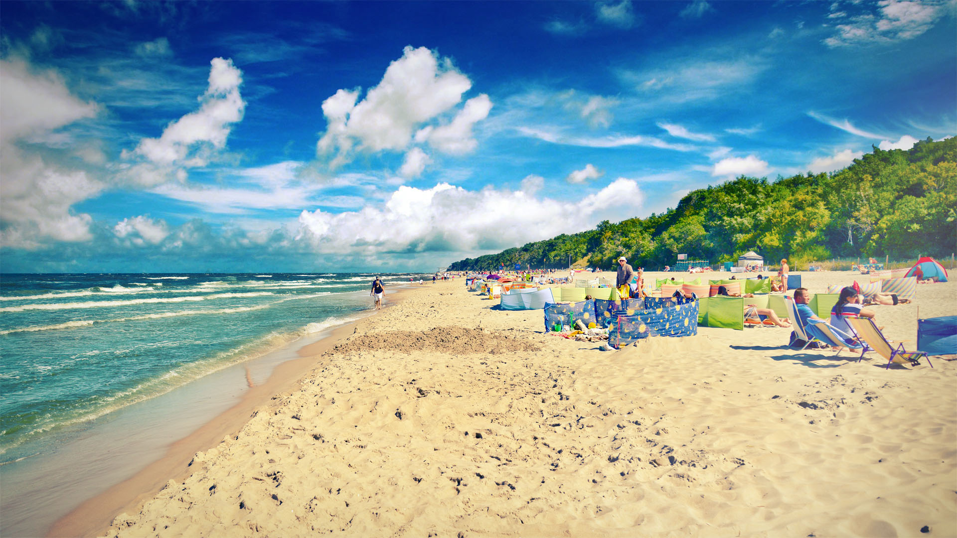Plaża w Pustkowie, na piasku opalający się turyści.